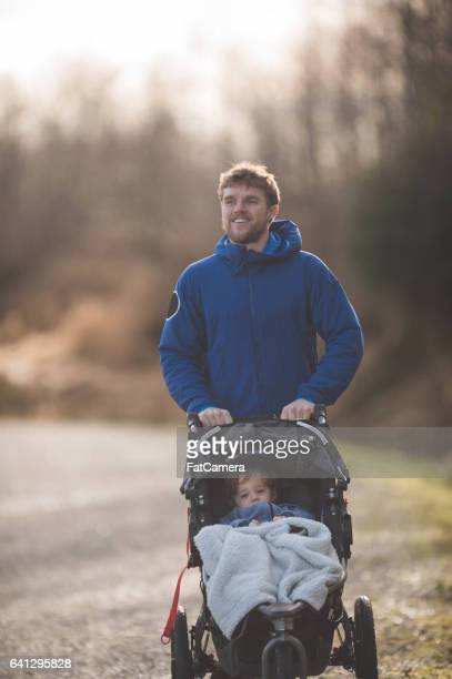 Young dad pushing baby stroller outside