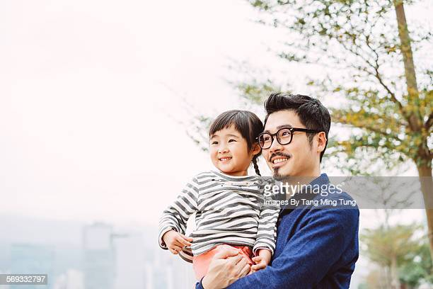 Young dad talking joyfully with daughter in a park