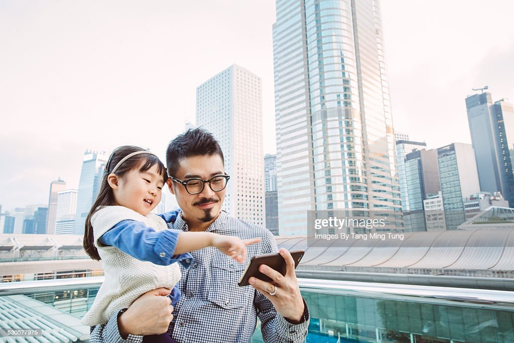 Young dad using smartphone joyfully with daughter : Stock Photo