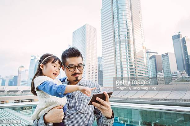 Young dad using smartphone joyfully with daughter
