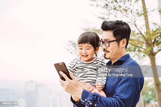 Young dad using smartphonejoyfully with daughter