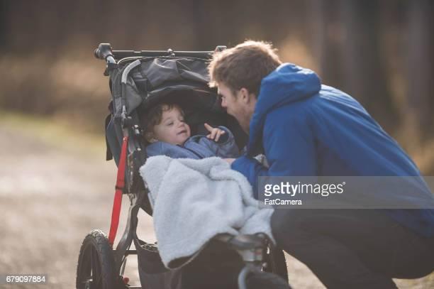 Ung pappa med pojken i barnvagn