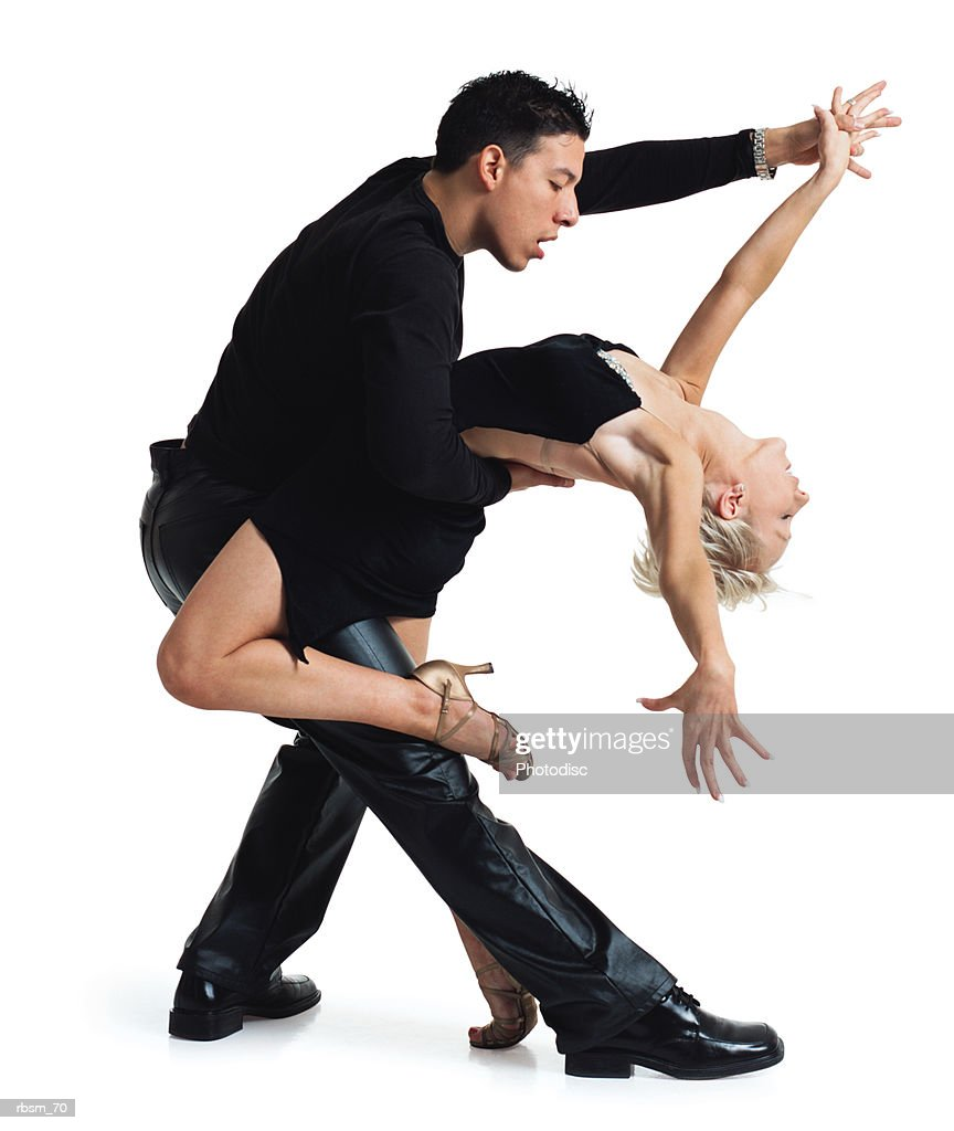 young dance couple latin male and a caucasian blonde both in a black hold each other in a tango pose : Foto de stock