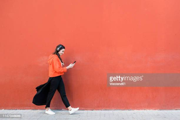 young dancer walking and using the phone and headphones in front of a red wall - a caminho imagens e fotografias de stock