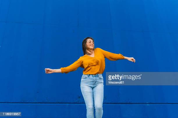 young dancing woman in front of a blue wall - jeans stock pictures, royalty-free photos & images