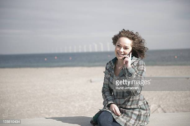 Young Danish woman, 26 years old, having a conversation on a cell phone outdoors at Amager Strandpark, Copenhagen, Denmark