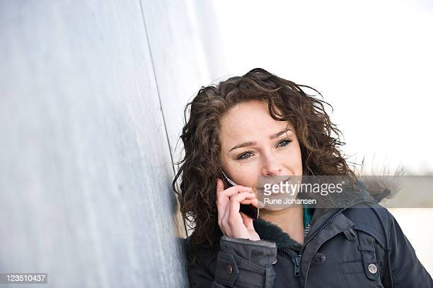 young danish woman, 26 years old, having a conversation on a cell phone outdoors at amager strandpark, copenhagen, denmark - 25 29 years stock pictures, royalty-free photos & images