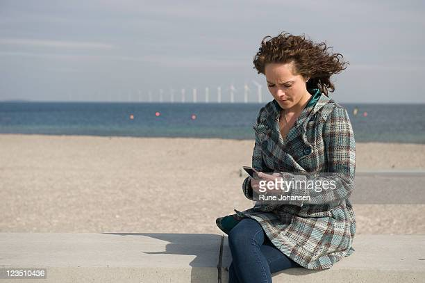 young danish woman, 26 years old, looking down at her cell phone outdoors at amager strandpark, copenhagen, denmark - 25 29 years stock pictures, royalty-free photos & images