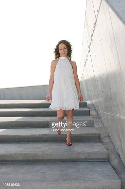 Young Danish woman, 26 years old, outdoors in a white cocktail dress walking down steps at Amager Strandpark, Copenhagen, Denmark