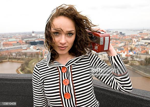 Young Danish woman, 26 years old, outdoors listening to music on a retro styled red radio, Copenhagen, Denmark