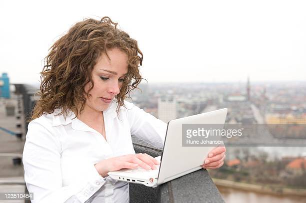 young, danish woman, 26 years old, outdoors on a small laptop, copenhagen, denmark - 25 29 years stock pictures, royalty-free photos & images