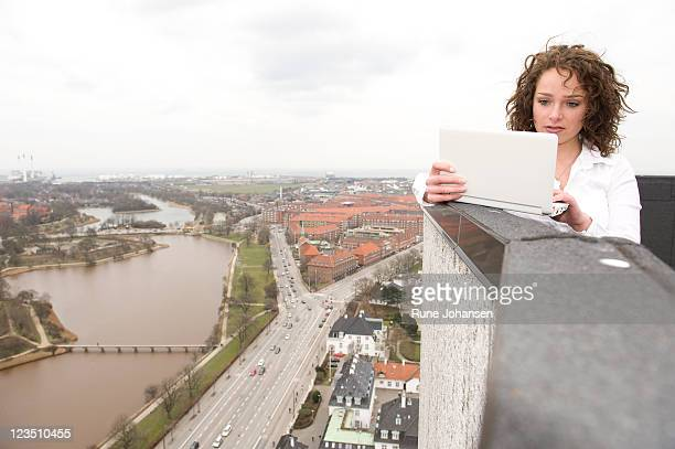 young, danish woman, 26 years old, outdoors on a small laptop, with views of copenhagen, denmark in the background - 25 29 years stock pictures, royalty-free photos & images