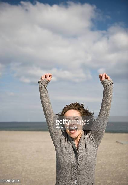 young danish woman, 26 years old, outdoors with arms outstretched in excitment, amager strandpark, copenhagen, denmark - 25 29 years stock pictures, royalty-free photos & images