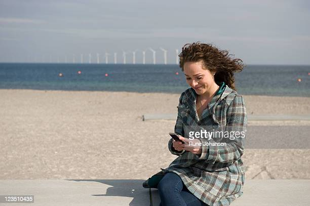 young danish woman, 26 years old, smiling while looking down at her cell phone outdoors at amager strandpark, copenhagen, denmark - 25 29 years stock pictures, royalty-free photos & images