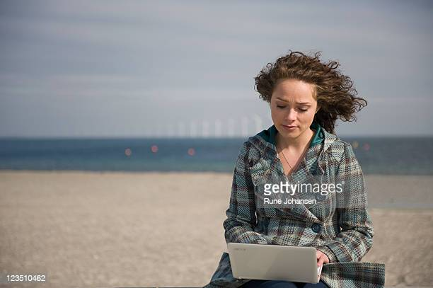 Young Danish woman, 26 years old, typing on laptop computer outdoors at Amager Strandpark, Copenhagen, Denmark