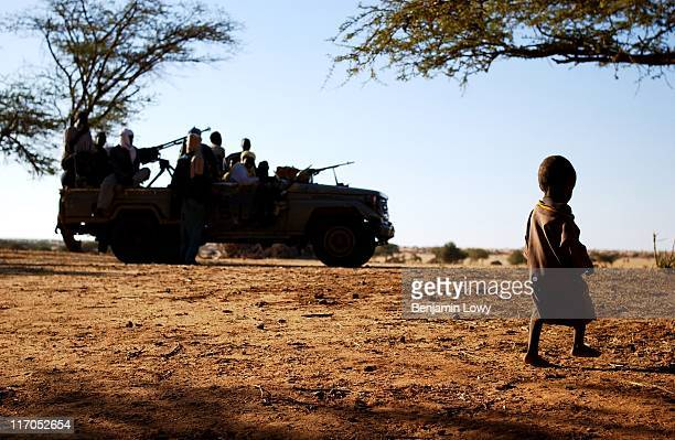 A young Darfurian refugee walks past an Sudan Liberation Army Land Rover filled with teenage rebel fighters on October 14 2004 in the violent North...