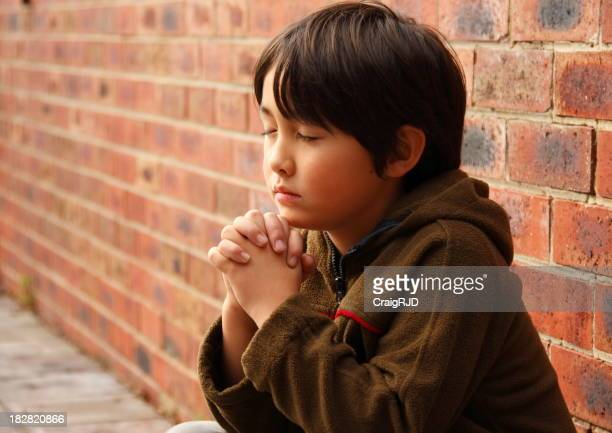 Young dark haired child praying next to a wall