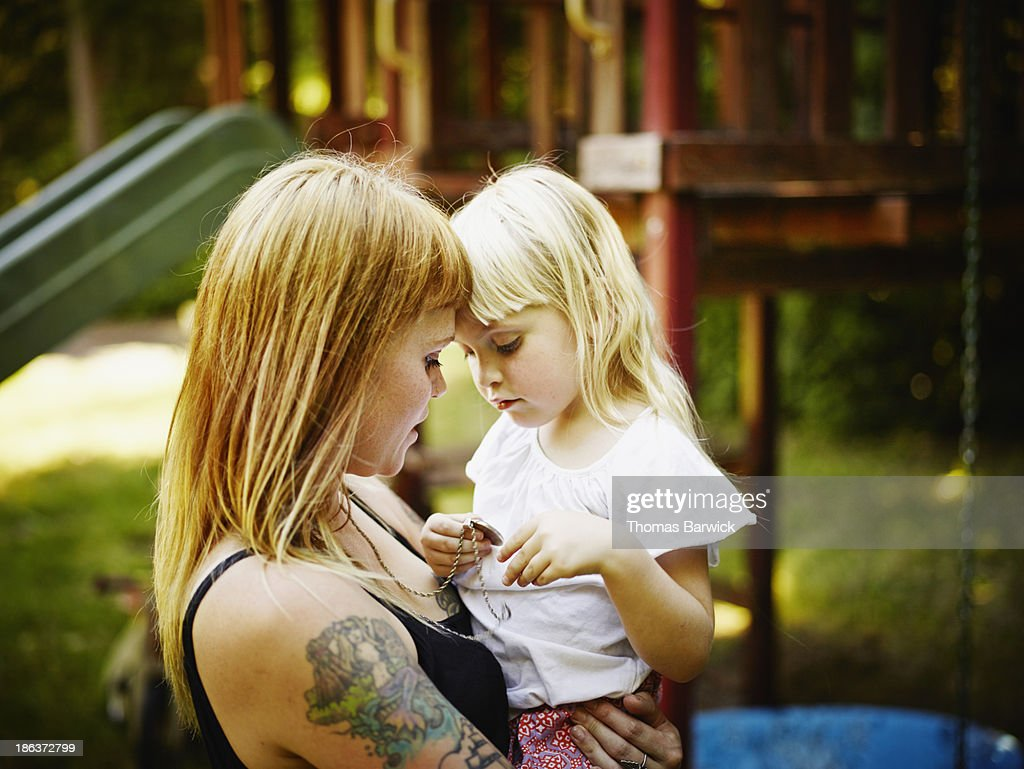 Young daughter being held by mother : Stock Photo