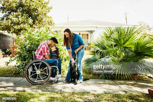 Young daughter giving father in wheelchair a kiss while standing in front of home with mother and dog