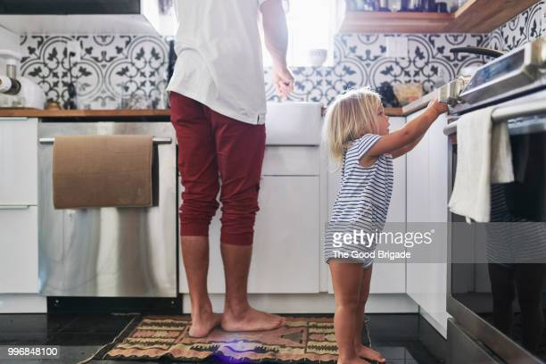 young daughter helping father in kitchen - adulte d'âge moyen photos et images de collection