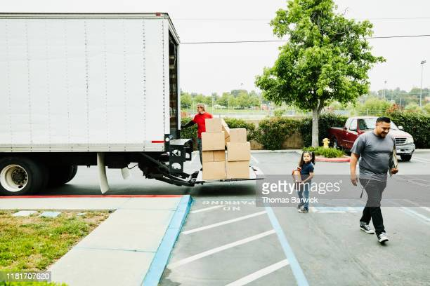 young daughter helping to carry items to moving truck while family moves - removal stock pictures, royalty-free photos & images