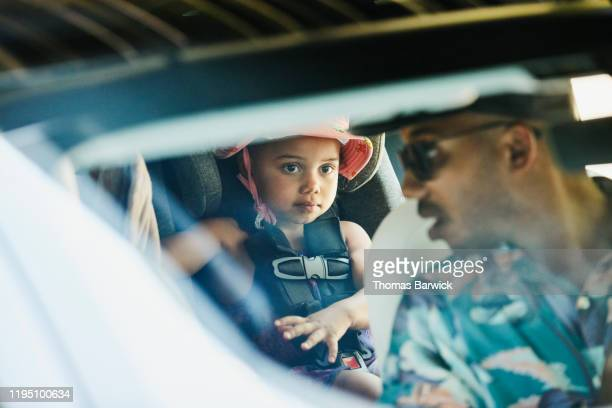 young daughter listening to father while buckling herself into car seat before road trip - blauwe riem stockfoto's en -beelden