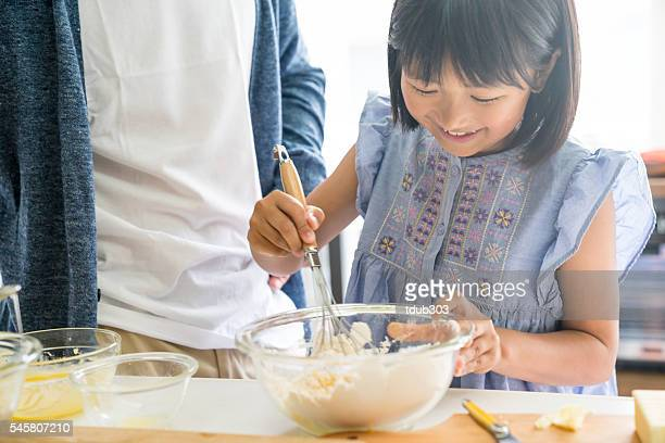 Young daughter looking happy while bonding and baking with father