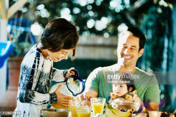 Young daughter pouring orange juice while sharing breakfast with family in backyard