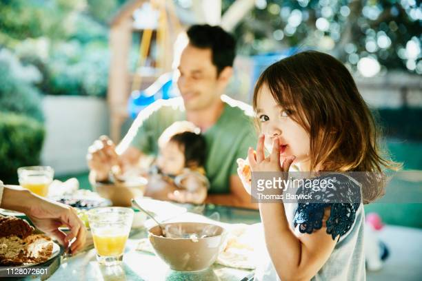 young daughter sharing breakfast with family at table in backyard - ontbijt stockfoto's en -beelden