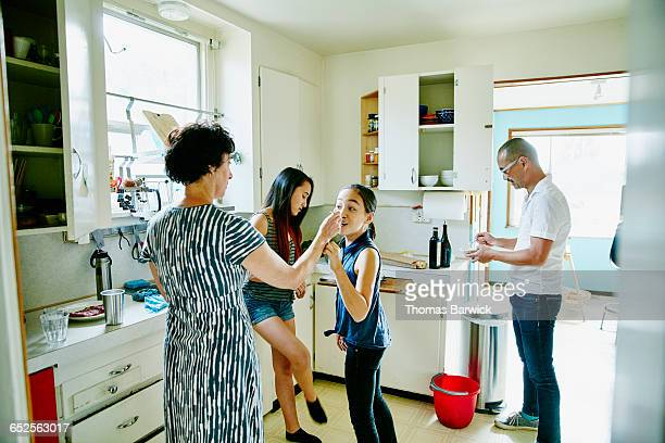 Young daughter tasting food in kitchen with family