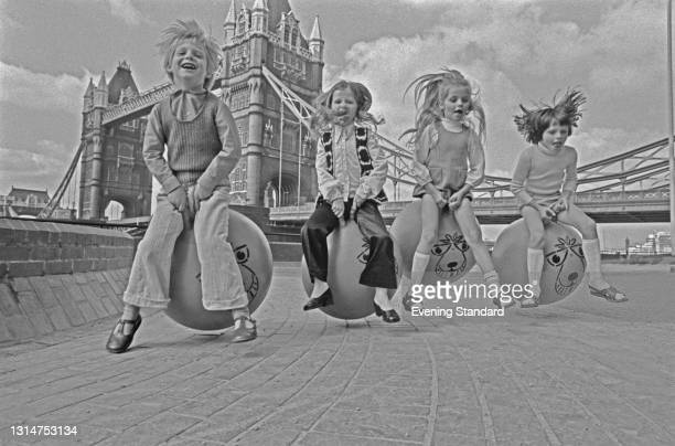 Young David Sammuels and friends bouncing on space hoppers near Tower Bridge in London, UK, 29th July 1974.
