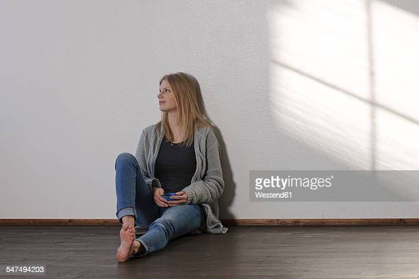 young daydreaming woman sitting on floor - donne bionde scalze foto e immagini stock
