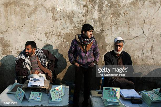 KABUL AFGHANISTAN – JANUARY A young dealer stands between makeshifts shops outside the traffic department in Kabul Obtaining a vehicle registration...
