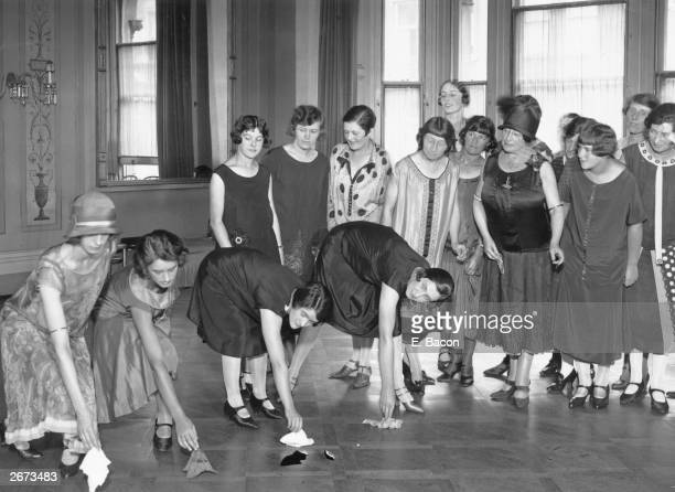 Young debutantes at a deportment school in Kensington London are shown the correct and incorrect way to retrieve a handkerchief from the floor in...