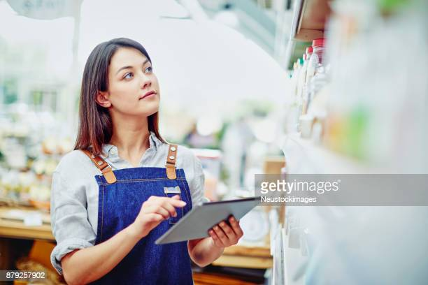 Young deli owner holding digital tablet while standing in store