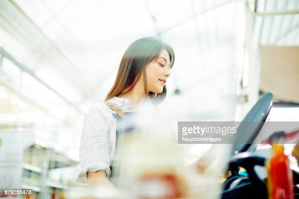 young deli owner using cash register in brightly lit shop - register stock photos and pictures