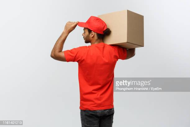 young delivery man holding cardboard box against white background - carrying stock pictures, royalty-free photos & images