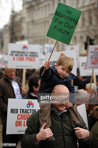 A young demonstrator holds a placard as pig farmers protest outside Downing Street in central London on March 3 2011 Pig farmers from around the...