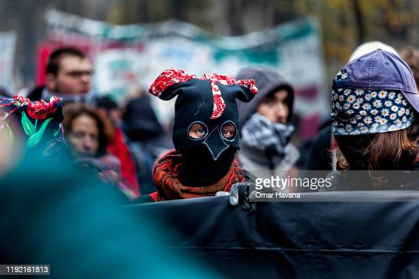 A young demonstrator wearing a balaclava walks in a demonstration during the first day of an indefinite general strike on December 05 2019 in Paris...