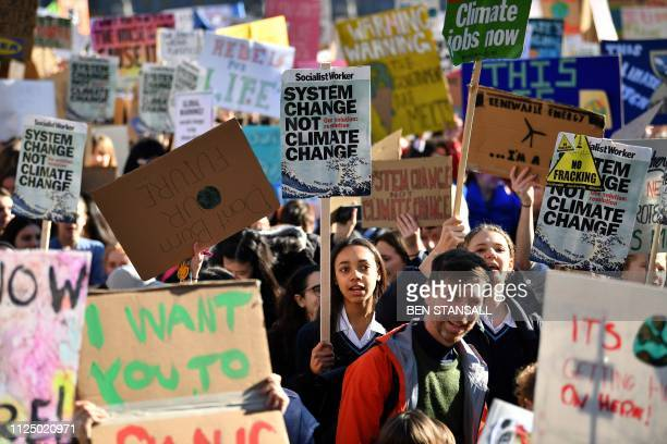 Young demonstrators hold placards as they attend a climate change protest organised by Youth Strike 4 Climate opposite the Houses of Parliament in...