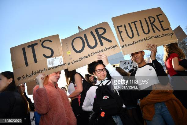 "Young demonstrators hold placards as they attend a climate change protest organised by ""Youth Strike 4 Climate"", opposite the Houses of Parliament in..."