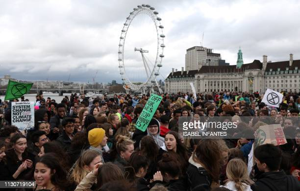 Young demonstrators hold placards as they attend Global Strike 4 Climate protest march on Westminster Bridge near the London Eye in central London on...