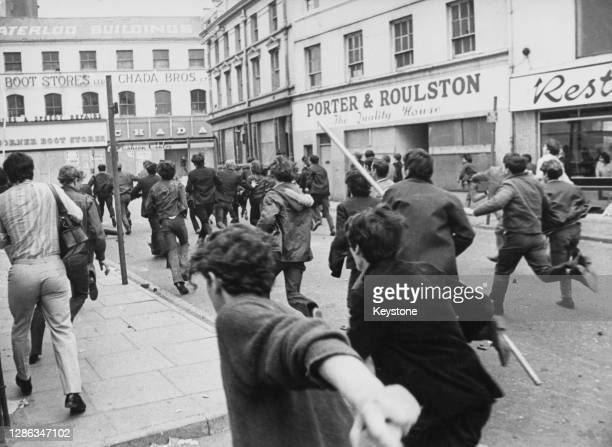 Young demonstrators running through the streets as trouble flared following the annual Apprentice Boys parade through the streets on Derry, Northern...
