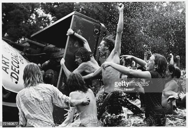 Young demonstrators shout and cheer as they overturn a truck trailer in the Reflecting Pool on the Mall facing the Washington Monument during the...
