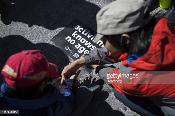 Young demonstrators stand over a sign that reads Activism Knows No Age on Pennsylvania Avenue during the March For Our Lives in Washington DC US on...