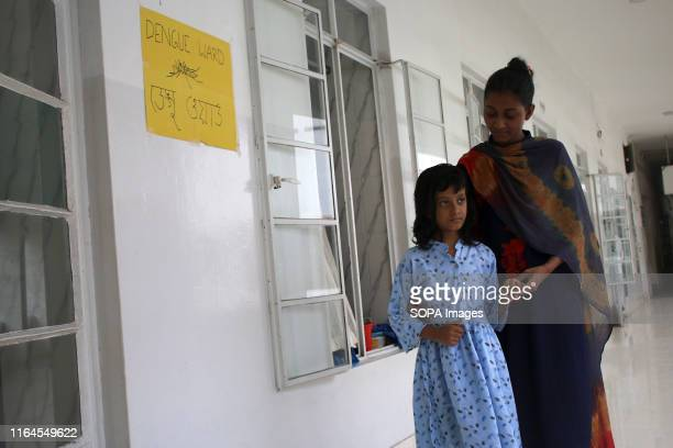 A young dengue patient walks at the hospital corridor with her elder sister at Holy Family Medical College and Hospital in Dhaka Bangladesh records...