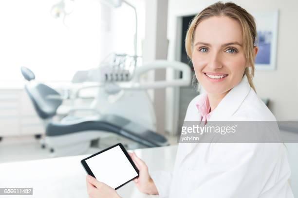 Young dental expert holding blank digital tablet