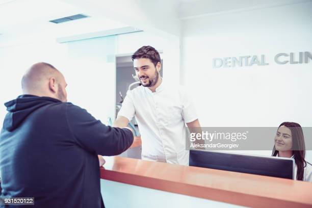 Young Dentist and His Assistant Make Appointment on Reception in Dental Clinic