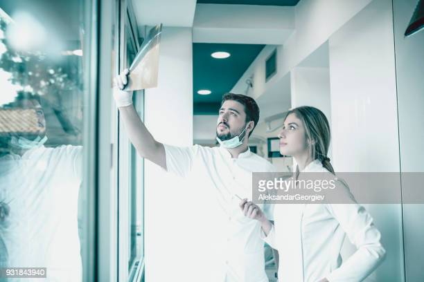 Young Dentist and Nurse Examining Patient's X-ray Image in Dental Clinic