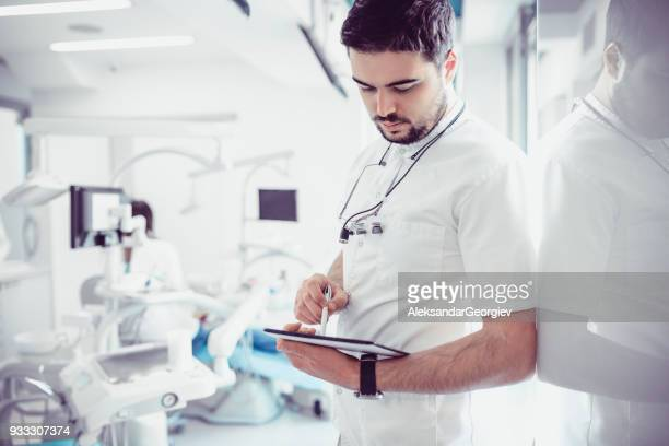 Young Dentist With Magnifier Glasses and Digital Tablet Working in Dental Clinic